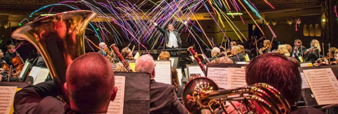 Photo of conductor and orchestra with fireworks